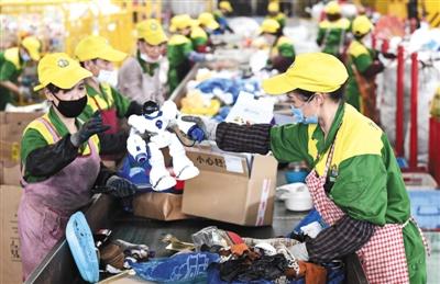 2019年7月8日,杭州余杭区的浙江虎哥环境有限公司分拣总仓,员工在流水线上分拣可回收垃圾。 图/视觉中国